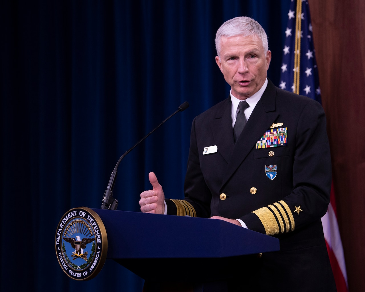 A man in a military uniform stands behind a lectern.  Behind him is an American flag.