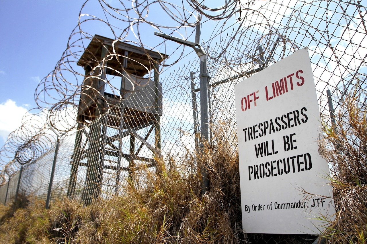 "An ""Off Limits"" sign hangs on a fence that is topped with concertina wire."