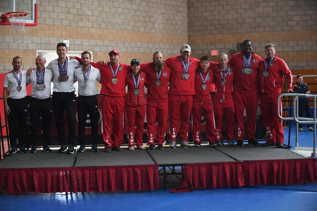 Athletes with teams France, left, Wounded Warrior Battalion-East, center, and Wounded Warrior Battalion-West, right, take home the bronze, silver, and gold medals, respectively, for the men's 100-meter relay race during the 2020 Marine Corps Trials at Marine Corps Base Camp Pendleton, Calif., March 10.
