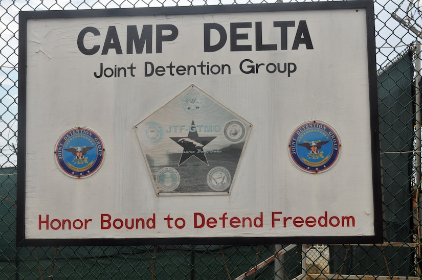 "A sign hangs on a fence. It reads ""Camp DELTA. Joint detention group.  Honor Bound to Defend Freedom."""