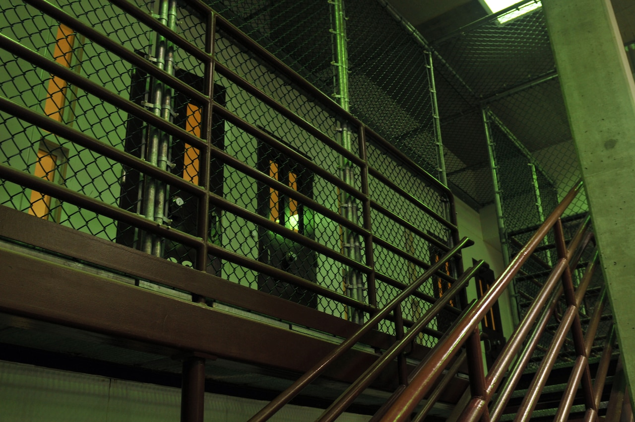 A metal staircase ascends to a caged area with detention facility cells.