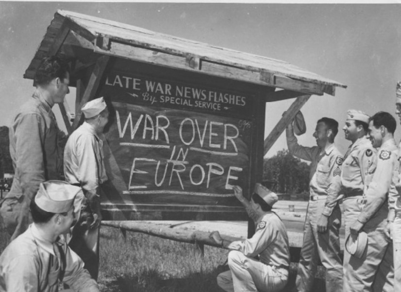 Troops smile as the read a message on a large board.