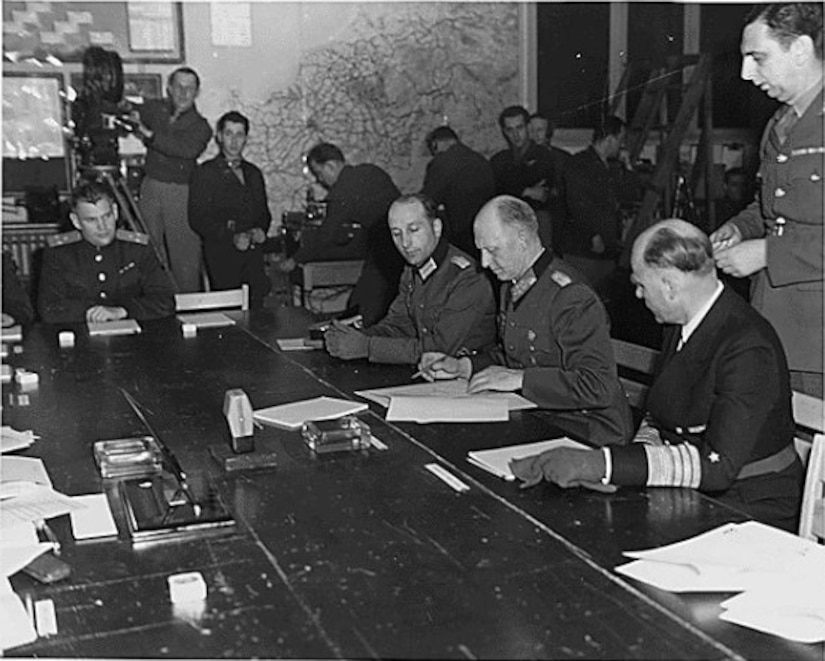 A German officer signs surrender papers.