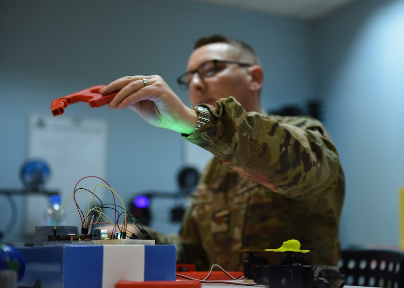U.S. Air Force Maj. Kyle Boothe, U.S. Air Forces Central Command chief innovation officer, holds a 3D printed item during the AFCENT Innovation Summit in the 379th Air Expeditionary Wing's Desert Spark Lab at Al Udeid Air Base, Qatar, March 3, 2020. The AFCENT innovation summit brought together military and academic minds to discuss ways of increasing effectiveness and lethality via timeliness and data-driven decision making. (U.S. Air Force photo by Staff Sgt. Hope Geiger)