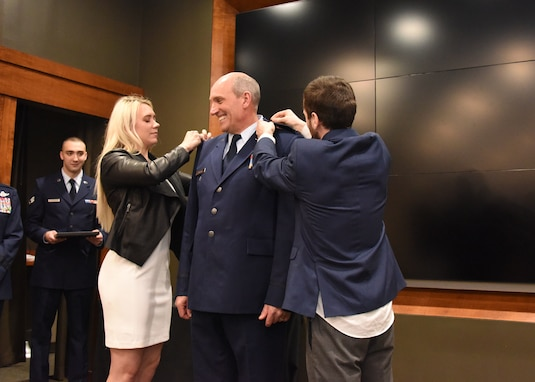 Daughter, Monica and son, Alex, pin eagles on newly promoted Illinois Air National Guard Col. William Miller, Director of Staff-Air, during a promotion ceremony March 8 at the Illinois Military Academy, Camp Lincoln, Springfield, Illinois.