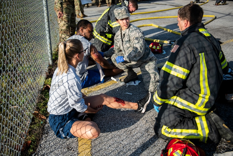 Tech. Sgt. Haley Lecomte, 325th Medical Group executive assistant, left, and Staff Sgt. Zachary Collins, 325th Operational Medical Readiness Squadron Ambulance Services Department technician, pretend to be medical trauma patients during an exercise at Tyndall Air Force Base, Florida, March 12, 2020. Senior Airman Ashley Deliz Aguilera, 325th OMRS ASD technician, center, and Staff Sgt. Jeffery Wells, 325th Civil Engineer Squadron fire department emergency medical technician, right, administered on scene medical treatment prior to patient transfer. (U.S. Air Force photo by Staff Sgt. Magen M. Reeves)