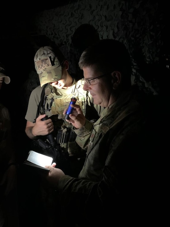 Chaplain (Maj.) John Russell from the 117th Air Refueling Wing, Sumpter Smith Joint National Guard Base, Birmingham, AL pauses with military personnel to read scripture during a recent deployment. (U.S. Air National Guard photo)