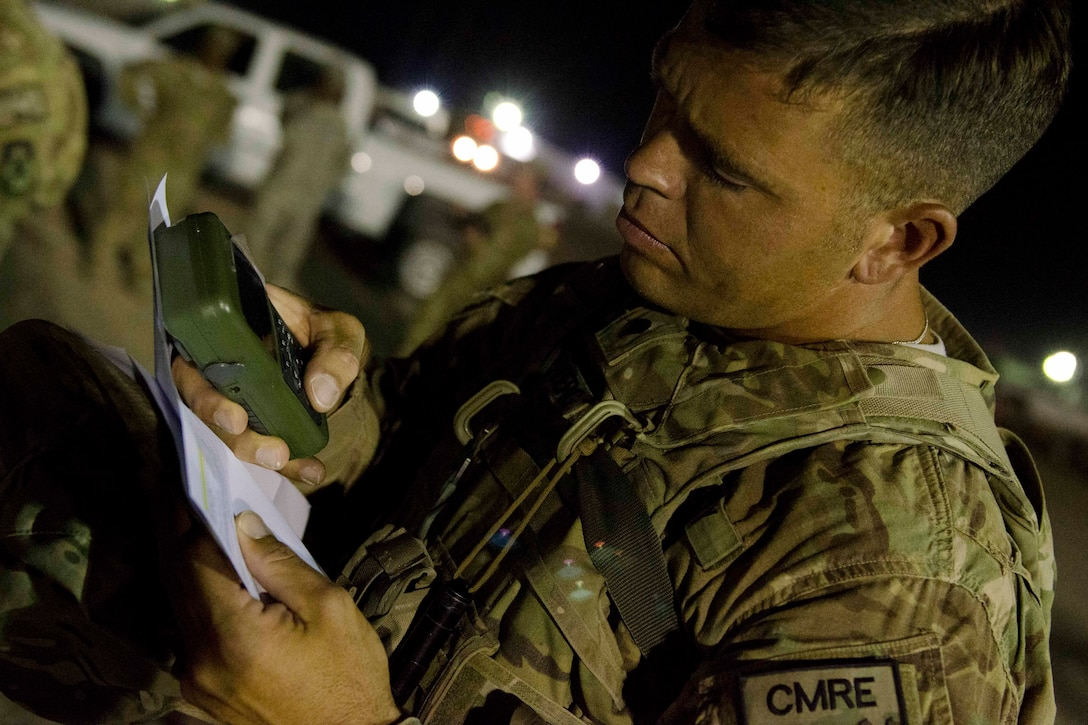 A soldier uses a handheld GPS device.