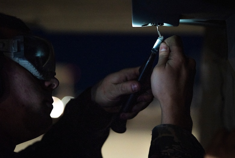 Airman tightens a wire on a jet.