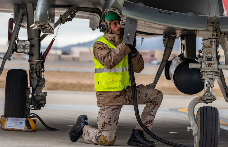 Airman connects a pump to a jet.