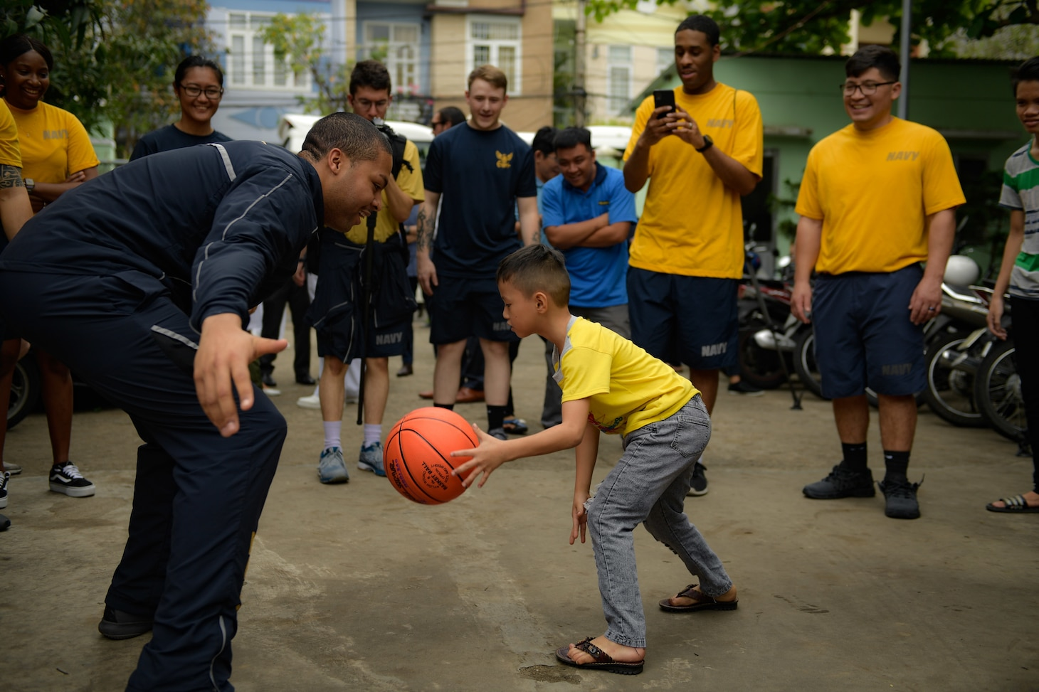 200306-N-YQ383-1567 VIETNAM (March 6, 2020) U.S. Navy Aviation Ordnanceman 3rd Class Khaden D. Vaughn, from Columbus, Ohio, plays basketball with a child at the Dorothea's Project Legacies Charity Center, Da Nang, Vietnam, during a community relations project organized by the aircraft carrier USS Theodore Roosevelt (CVN 71) March 6, 2020. Theodore Roosevelt and the Ticonderoga-class guided-missile cruiser USS Bunker Hill (CG 52) are in Vietnam for a port visit during their scheduled deployment to the Indo-Pacific.