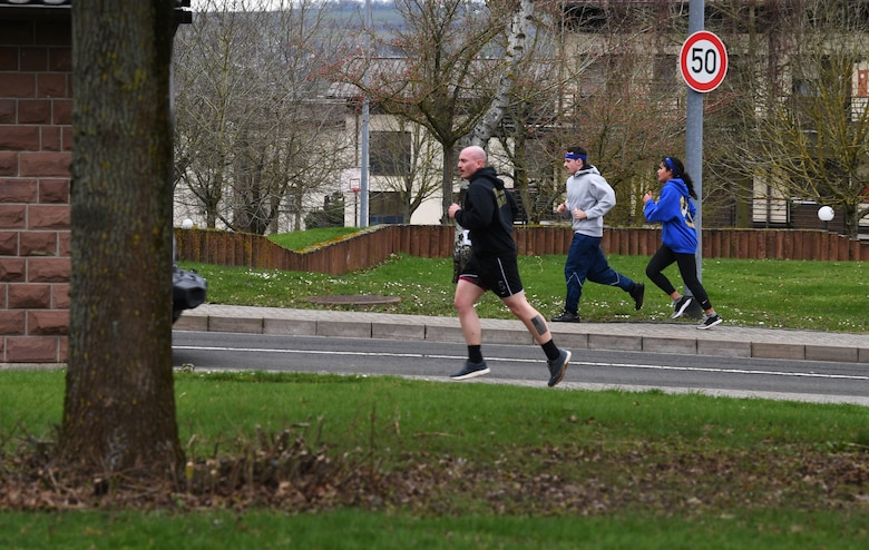 """Participants of the """"Run with Rosie"""" race run to the next location at Spangdahlem Air Base, Germany, March 12, 2020. The race consisted of clues and trivia that led participants to different locations around the base. (U.S. Air Force photo by Airman 1st Class Alison Stewart)"""