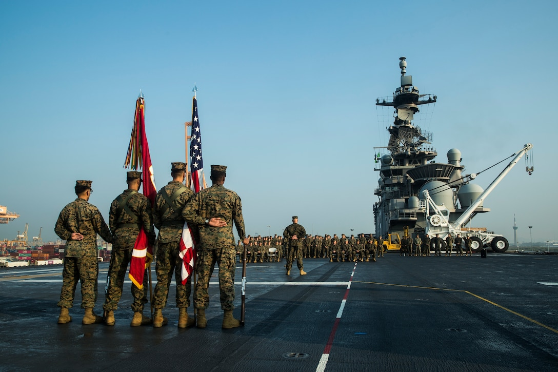 Marines stand at parade rest during the relief and appointment ceremony of Sgt. Maj. Edwin Mota, offgoing 31st Marine Expeditionary Unit (MEU) sergeant major, and Sgt. Maj. Douglas Gerhardt, oncoming 31st MEU sergeant major, aboard amphibious assault ship USS America (LHA 6) March 11.