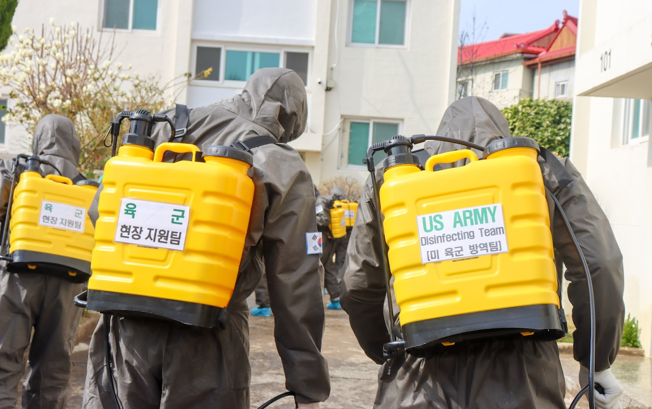 People in chemical suits spray disinfectant.