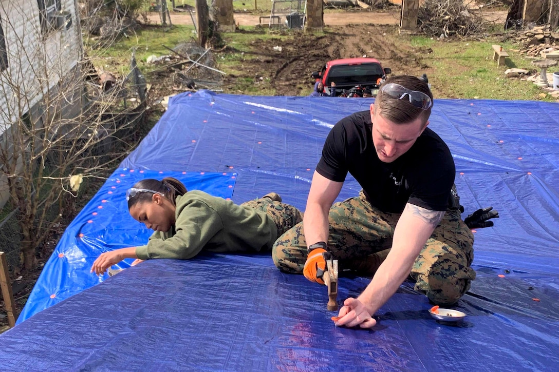 Two Marines secure tarps on a roof.