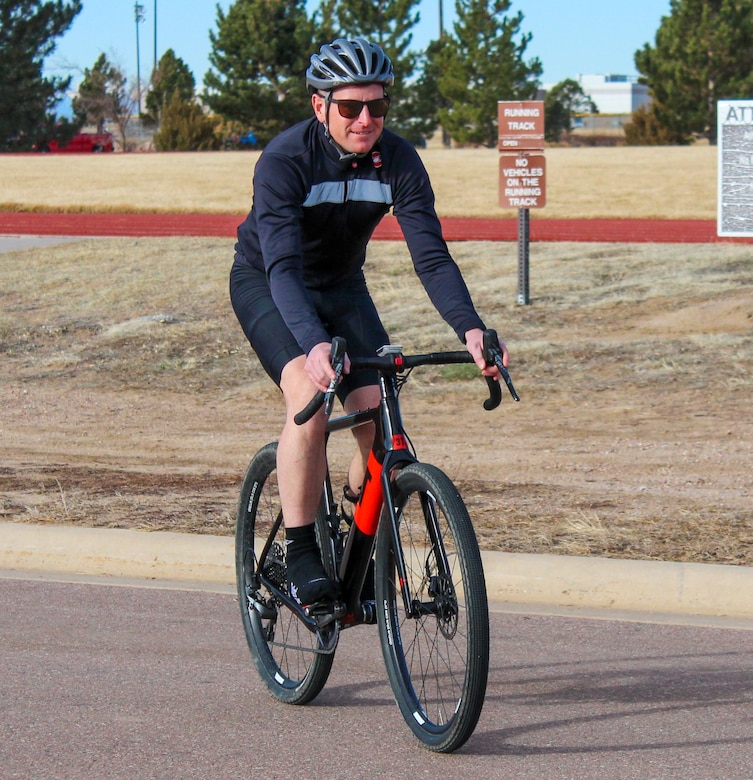 Maj. Jeffrey Lucy, U.S. Space Command Joint Intelligence and Security collections manager, rides his bike near the fitness center March 11, 2020 at Schriever Air Force Base, Colorado. Participants in the Lazyman Triathlon had to swim 2.4 miles, cycle 112 miles and run 26.2 miles within one month. (U.S. Air Force photo by Marcus Hill)
