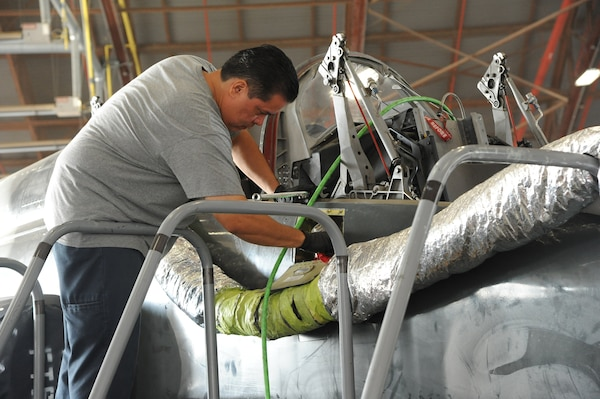 An Aircraft maintainer standing on a platform to conduct maintenance on a T-38 cockpit inside a hangar.