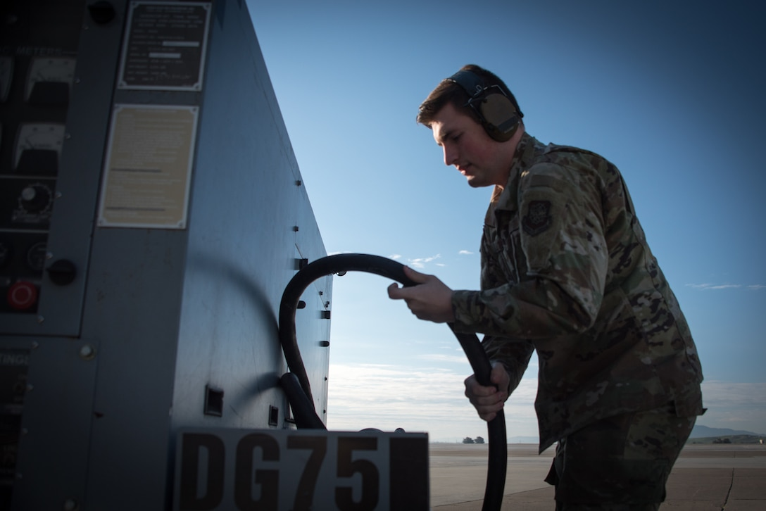 A crew chief stows a cable on a power cart on the flight line