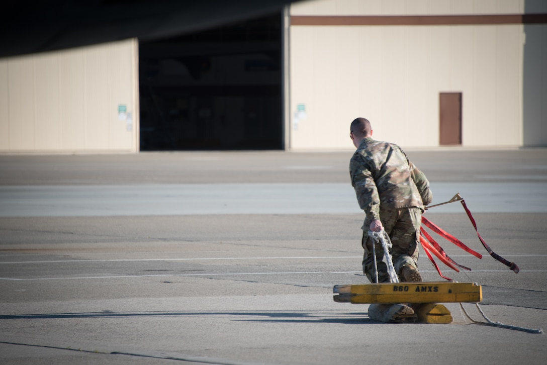 A crew chief pulls chocks from a KC-10 Extender prior to takeoff