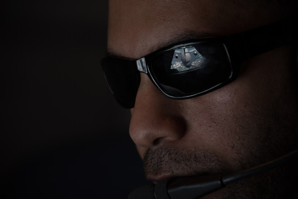 Sunglasses worn by a boom operator show the reflection of a KC-10 boom connecting with another KC-10 Extender
