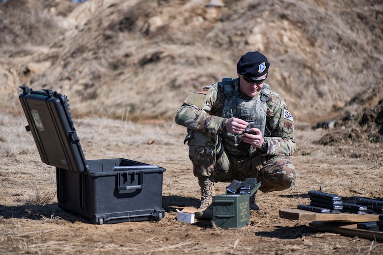 "Master Sgt. loads magazines during ""shoot, move and communicate"" drills"