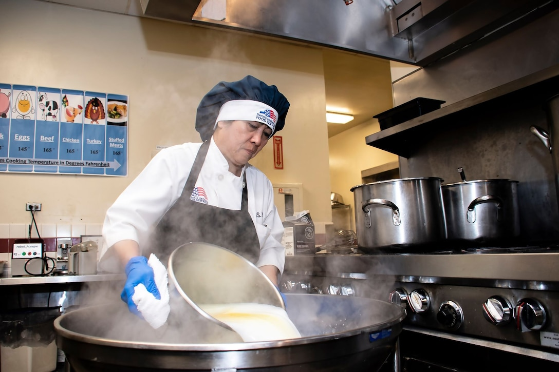Praxedes Miller, 60th Force Support Squadron cook, makes a serving of mashed potatoes before a lunch service March 11, 2020, at Travis Air Force Base, California. Miller's more than 30 years of kitchen experience come in handy during the base's meal services, which support thousands of Airmen. (U.S. Air Force photo by Senior Airman Christian Conrad)
