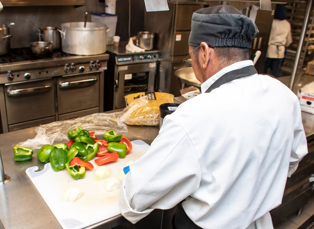 Miguel Santos, 60th Force Support Squadron cook, prepares vegetables ahead of a lunch service March 11, 2020, at Travis Air Force Base, California. Santos works at the base's dining facility, the Monarch. (U.S. Air Force photo by Senior Airman Christian Conrad)