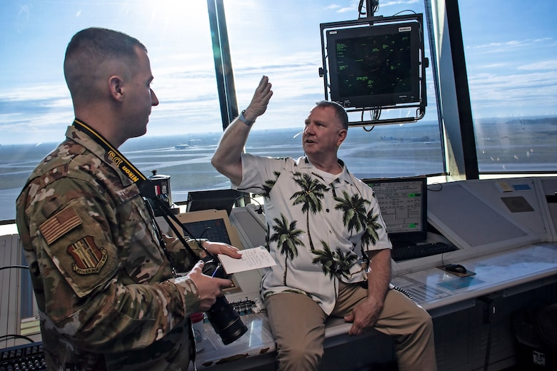 U.S. Air Force Senior Airman Jonathon Carnell, 60th Air Mobility Wing Public Affairs photojournalist, left, listens to Kenneth Breedlove, 60th Operations Support Squadron air traffic controller, explain aspects of tower operations March 11, 2020, at Travis Air Force Base, California. Breedlove also discussed the value of simulation training for air traffic controllers where trainees are allowed the space to fail in a low-threat environment in order to learn best practices. (U.S. Air Force photo by Senior Airman Christian Conrad)