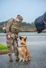 A military working dog handler stands with their military working dog.