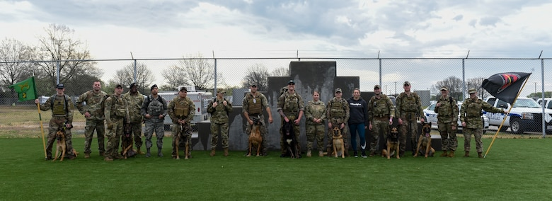 A group of military working dog handlers and their dogs pose for a photo after a ruck march.
