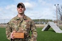 A man holds a wooden box.