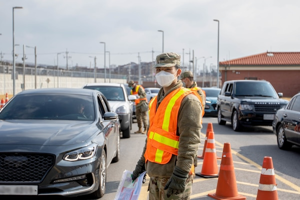 Soldier wearing gloves and a surgical mask stops vehicles at a checkpoint.
