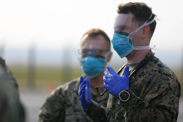 Two men wearing gloves and surgical masks over their noses and mouths look into the distance.