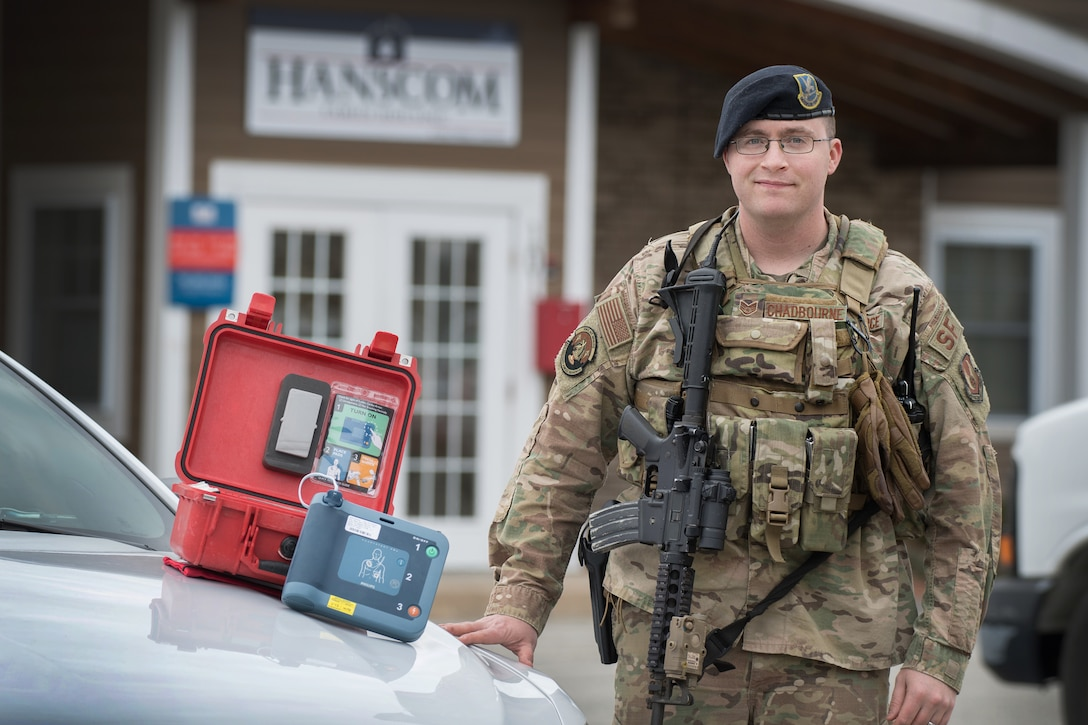 Staff Sgt. Humphrey Chadbourne, 66th Security Forces Squadron patrolman, stands by his cruiser with an automated external defibrillator machine at Hanscom Air Force Base, Mass., March 12. Earlier this year, Chadbourne was the first to respond to a medical emergency where his rapid and decisive actions ultimately saved the life of a contractor who suffered a heart attack on base.  (U.S. Air Force photo by Jerry Saslav)
