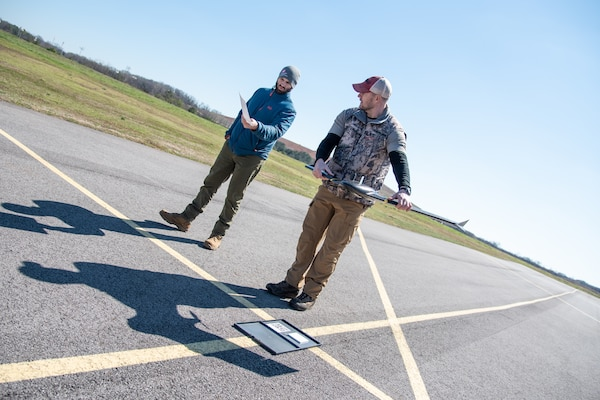 Brian Roden, left, a project manager and civil engineer with the U.S. Army Engineering and Support Center, Huntsville, works with Ryan Strange, research physical scientist with the U.S. Army Corps of Engineers' Aviation and Remote Systems Program and Huntsville Center's Unmanned Aircraft Systems Site Development Branch, to calibrate a sensor on the senseFly eBee X fixed-wing unmanned aircraft system before takeoff at the Rocket City Radio Controllers complex in southeast Huntsville, Alabama, during an unmanned aircraft systems capabilities review Feb. 27, 2020.