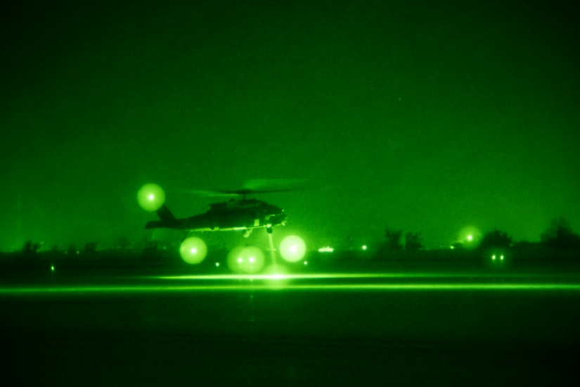 As seen through night vision, a helicopter lands.