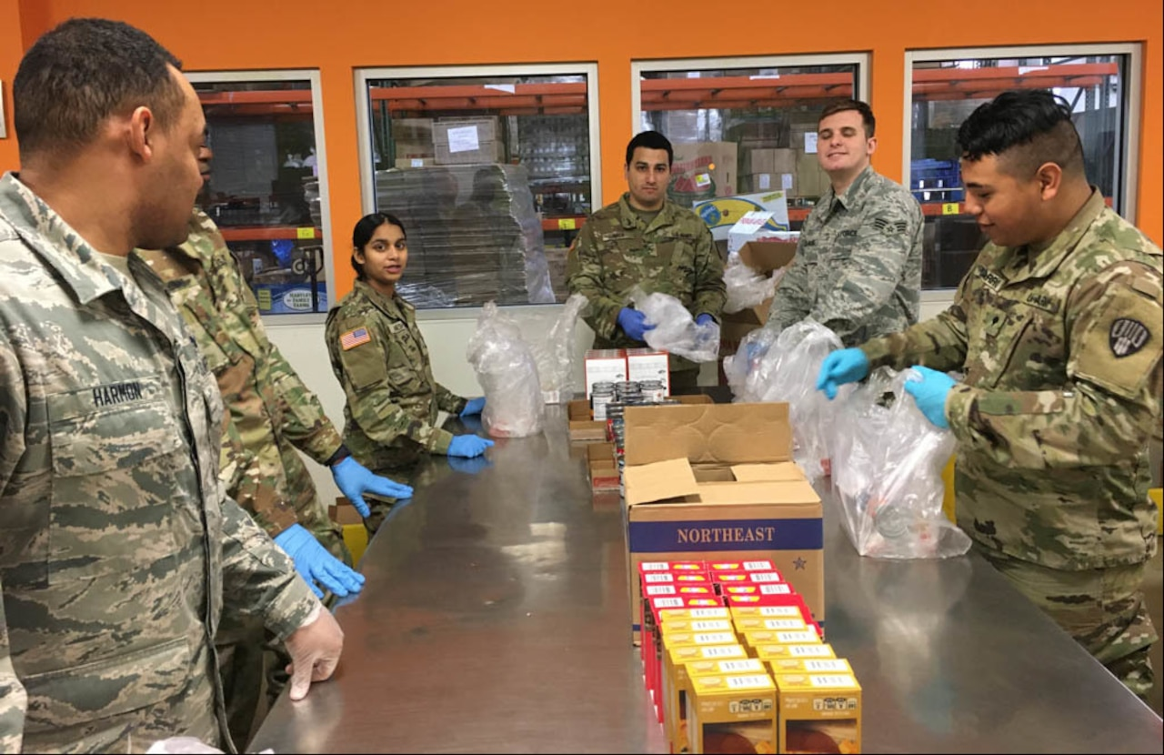 Soldiers, airmen gather food packages.