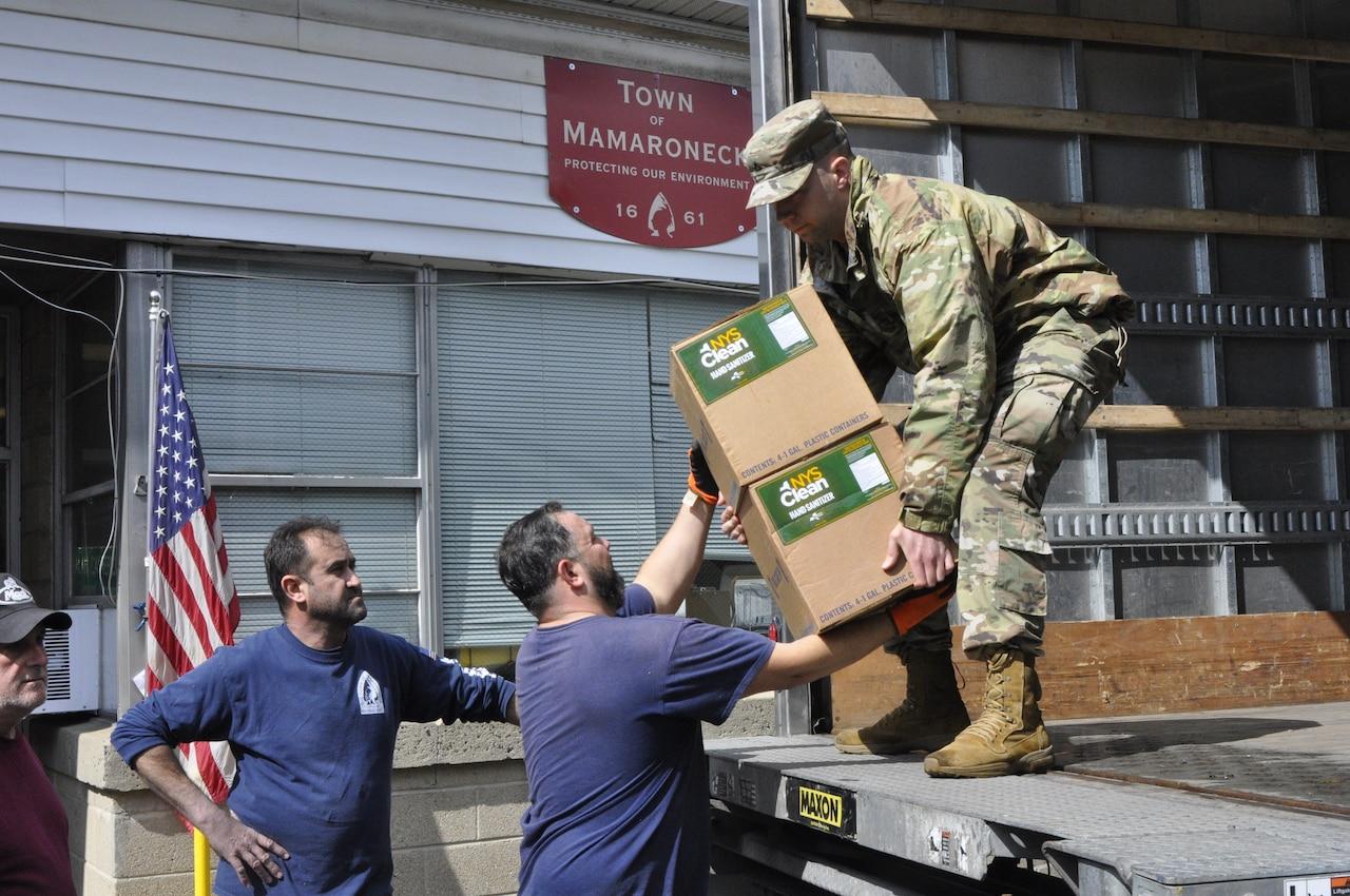 Guardsman unloads supplies from truck.