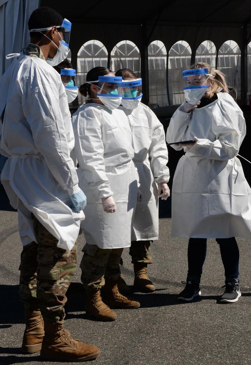 Guardsmen in medical garb receive briefing.
