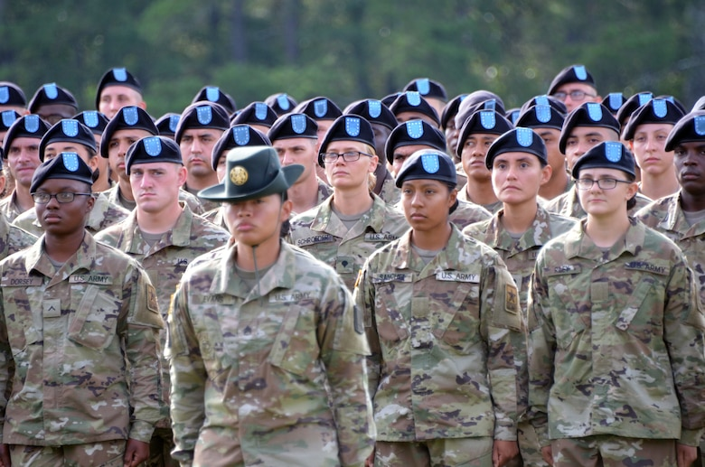Men and women in green camouflage uniforms and black berets with blue flashes stand behind a woman in green camouflage uniform and green hat.