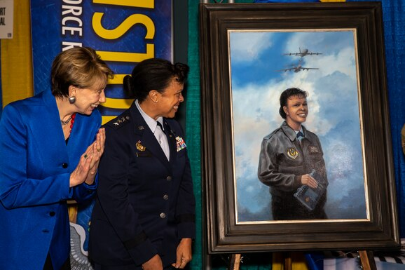 Secretary of the Air Force Barbara Barrett and Lt. Gen. (ret.) Stayce Harris look on at the unveiling of Harris' painting at the Women in Aviation International conference