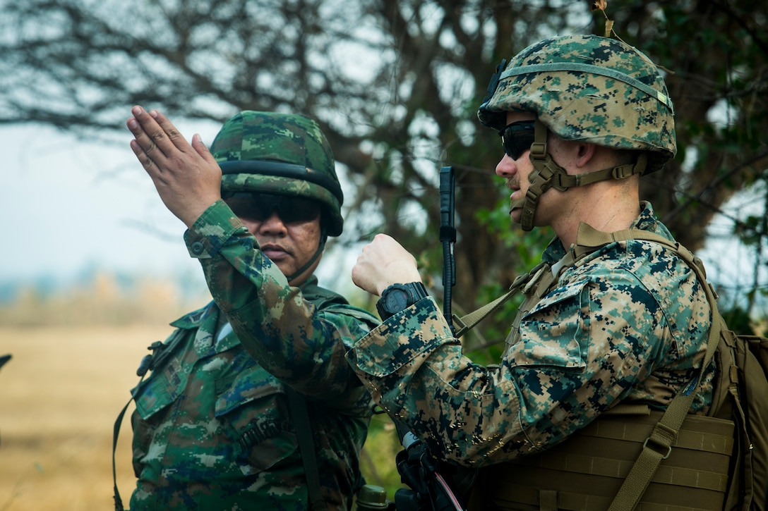 A Royal Thai Marine talks with a U.S. Marine during a combined joint High Mobility Artillery Rocket System rapid insertion as part of Cobra Gold 2020, at Chandy Range Kingdom of Thailand, March 2.