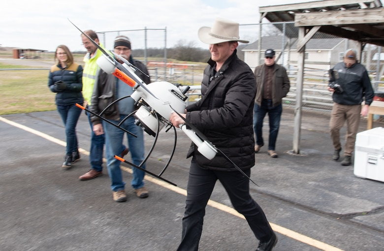 Navigational Electronics Inc. demonstrator and subject-matter expert Ross Kenney carries the Microdrones MD4-1000 unmanned aircraft system to a takeoff point during a capabilities review at the Rocket City Radio Controllers complex in southeast Huntsville, Alabama, Feb. 27, 2020.