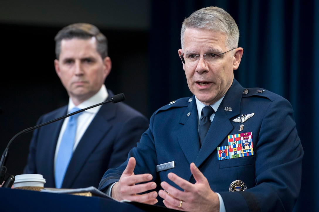 An airman speaks at a lectern while a civilian watches in the background.