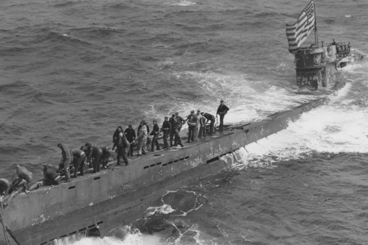 People walk on a submarine.