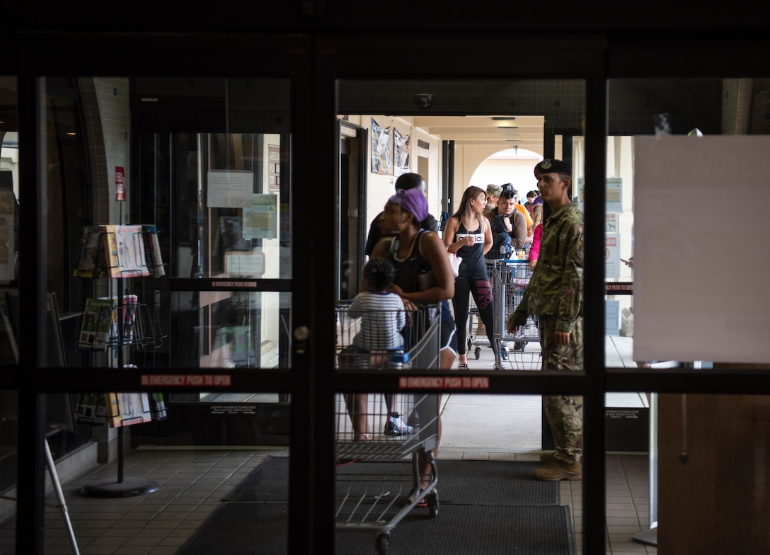 Service members and spouses assigned to Andersen Air Force Base and Naval Base Guam wait in line to enter the Andersen Commissary at AAFB, Guam, March 17, 2020.