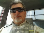 Selfie of man in a bulletproof vest in a truck on deployment.