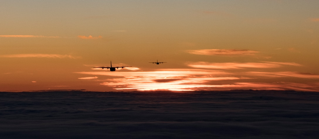 Two C-130J Super Hercules aircraft assigned to the 37th Airlift Squadron fly over Germany at sunset.