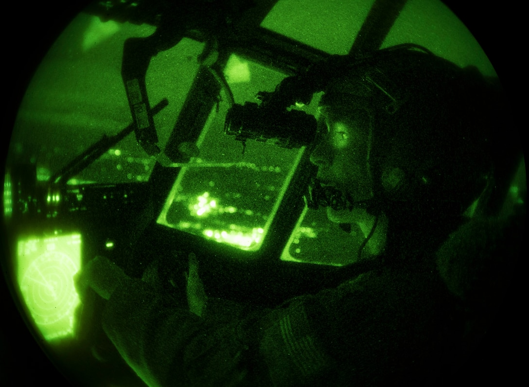 U.S. Air Force Maj. Mary Baldwin uses night vision equipment to fly a C-130J Super Hercules aircraft at night.