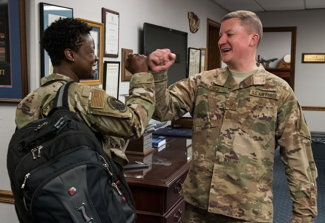 Col. Matthew Jones, 436th Airlift Wing commander, greets Col. Angenene Robertson, Air Mobility Command director of manpower, personnel and services, with a fist bump March 11, 2020, on Dover Air Force Base, Delaware. Robertson visited the base for an immersion, where she learned in-depth details about many organizational missions and day-to-day operations. (U.S. Air Force photo by Roland Balik)